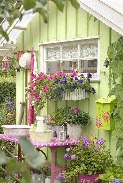 An adorable spring-green garden shed decked out with lots of containers of flowers and gardening accessories. A small pink table rests against one outer wall, a great workstation!