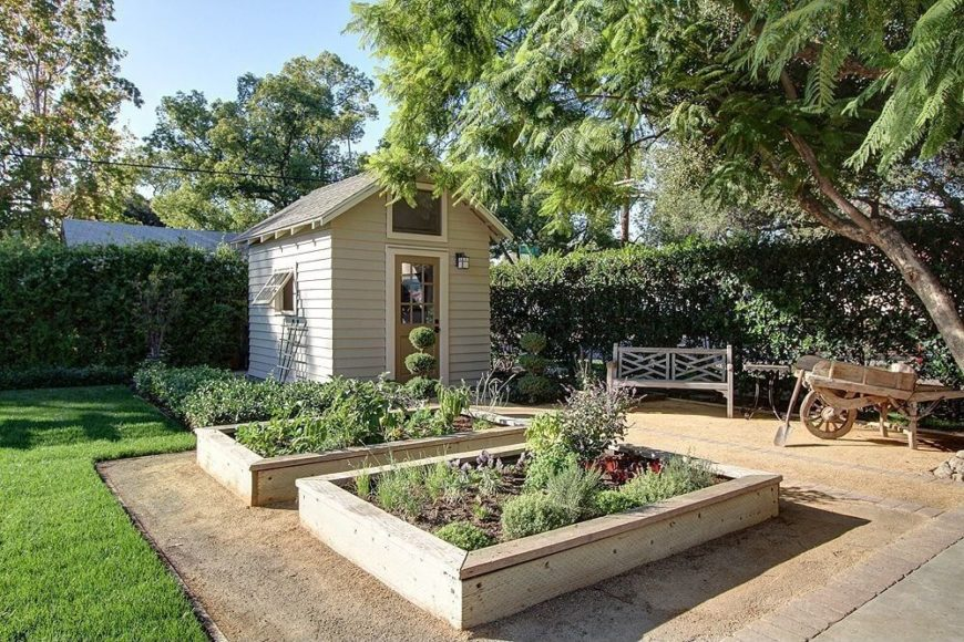 This garden shed is built at the corner of the property, facing the raised wooden beds of vegetables and herbs nearby. The designated garden area is kept visually separate from the grass lawn