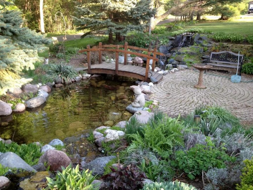 This simple Asian style footbridge leads from a circular patio to a small trail through the rest of the garden over a small pond fed by a stream.