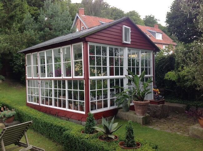 An Adorable Red And White Greenhouse With A Small Stone Walkway Out Front.  The Greenhouse