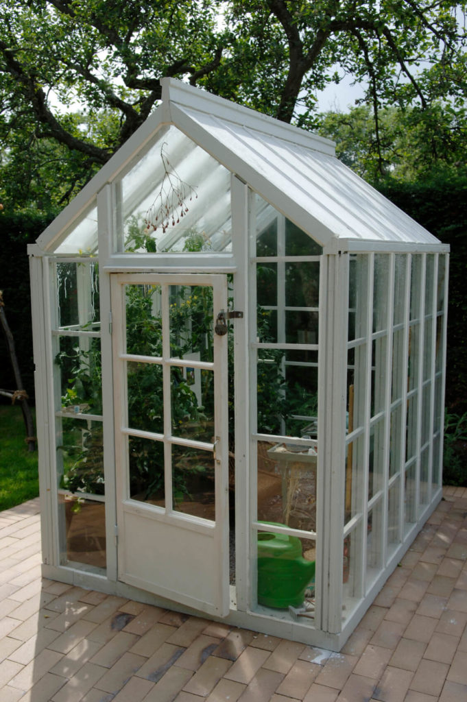 A small white greenhouse the doubles as a gardening shed. This structure is placed upon the brick patio.