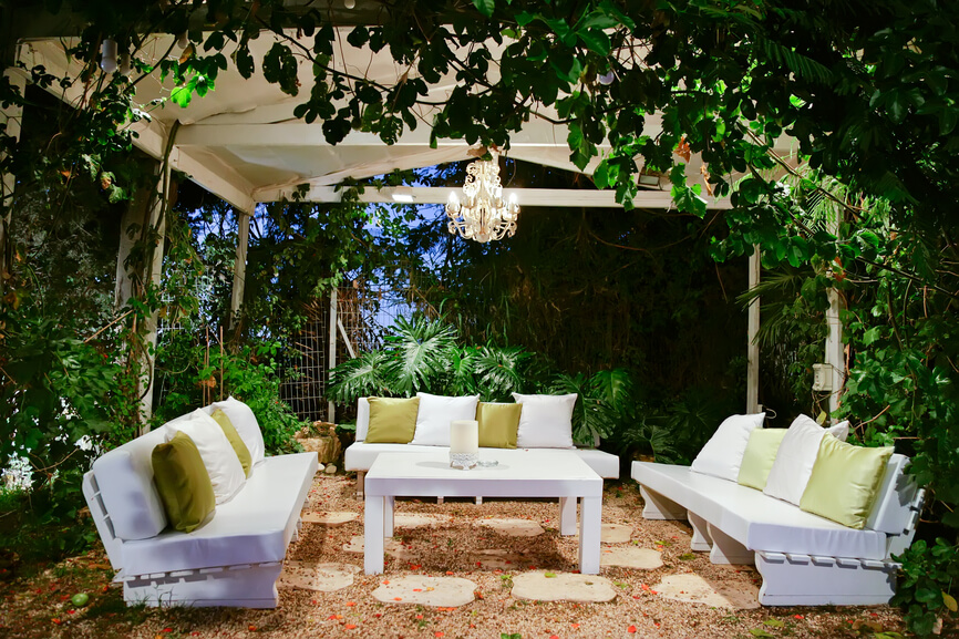 Another secluded patio underneath a large white pavilion. A small chandelier hangs from the center above the coffee table.