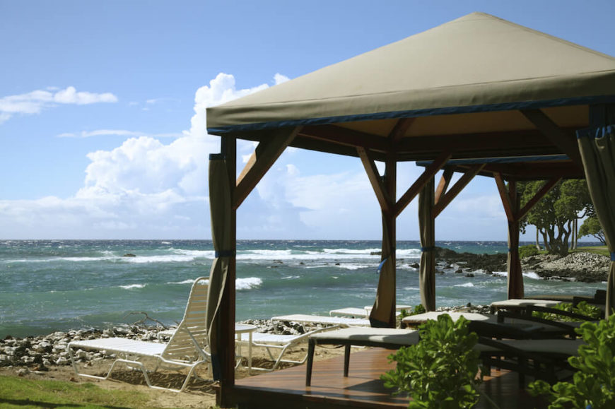 A beachside pavilion with lots of lounge chairs beneath. The rocky shores lead into the pounding surf.