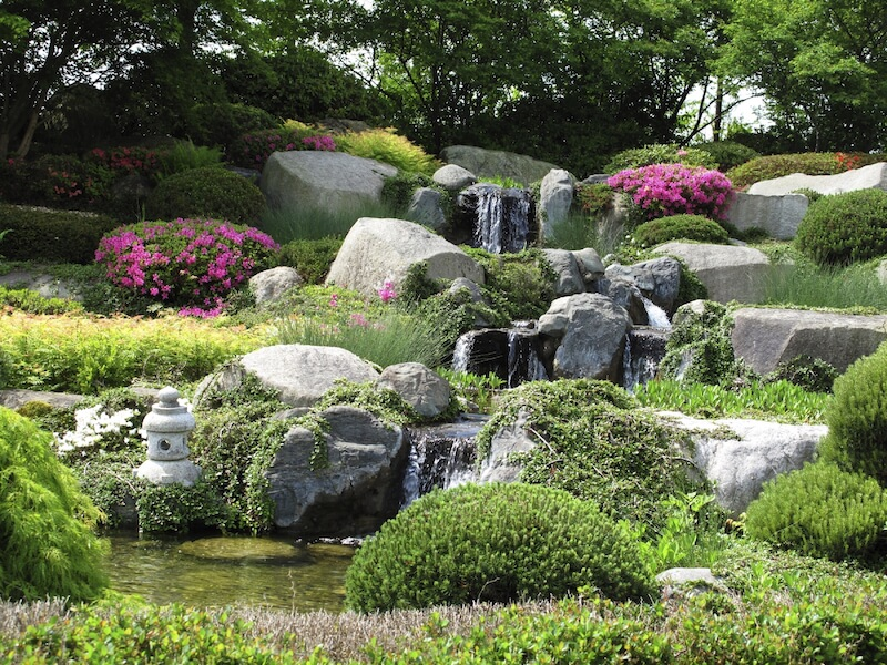 The enormous boulders in this garden are used to facilitate a lovely multi-tiered waterfall. The land between is filled with bushes, water-loving plants, and some flowering shrubs.