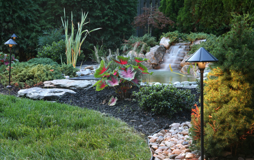 A large stone waterfall flows into a backyard pond with stepping stones leading up to the bank.