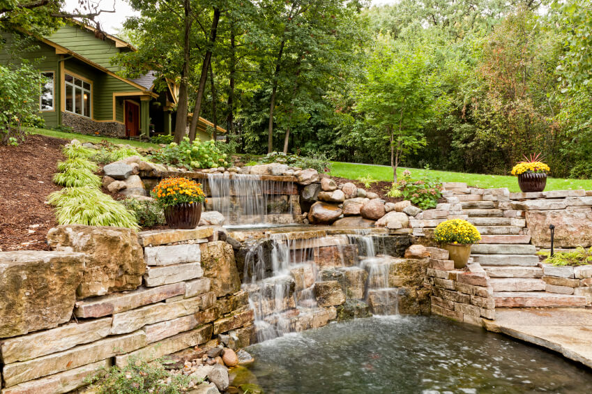 A massive backyard waterfall that leads down from the main yard to a lower patio that is surrounded by water.