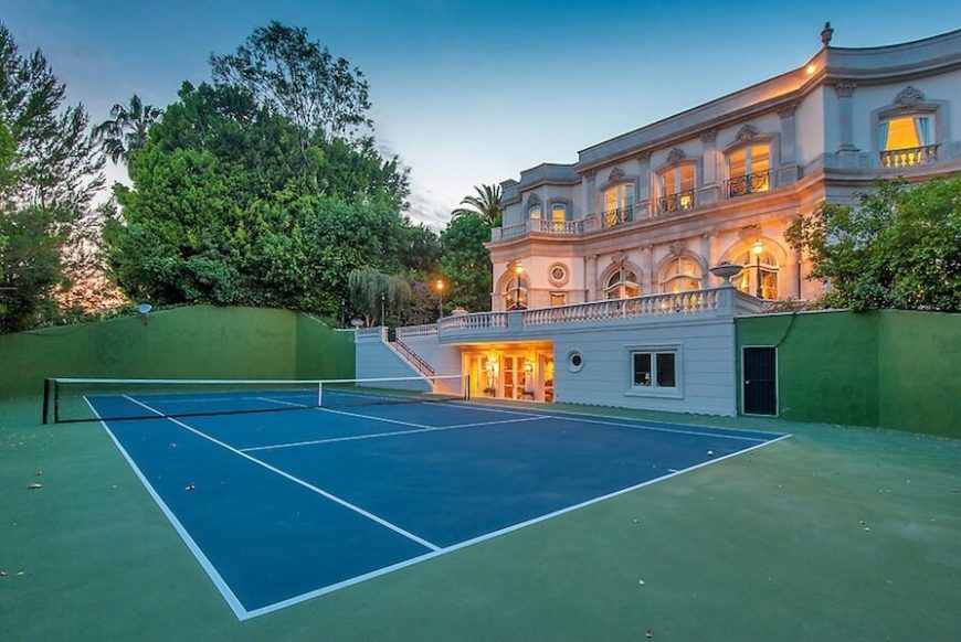 This massive standard tennis court has its own entrance directly from the basement of the classically styled mansion in the background.