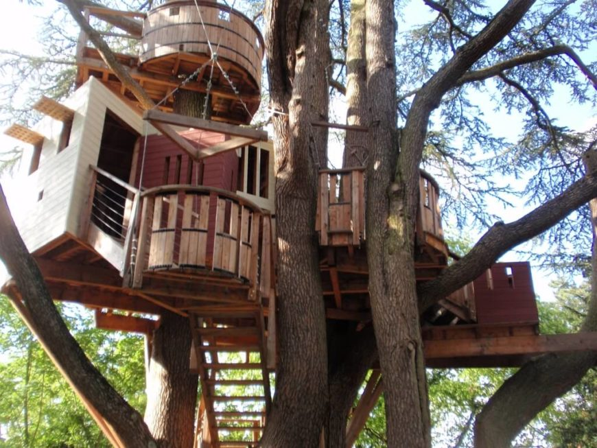 This is a real tree house, with an elevator, shutters, and even a lookout point!
