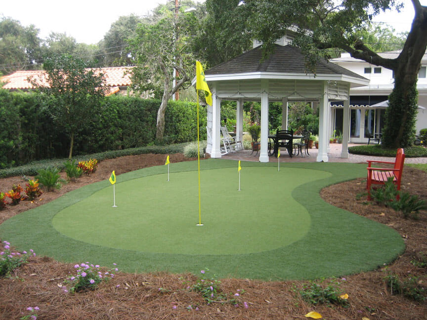 This small putting green is near the gazebo and a brick walkway.
