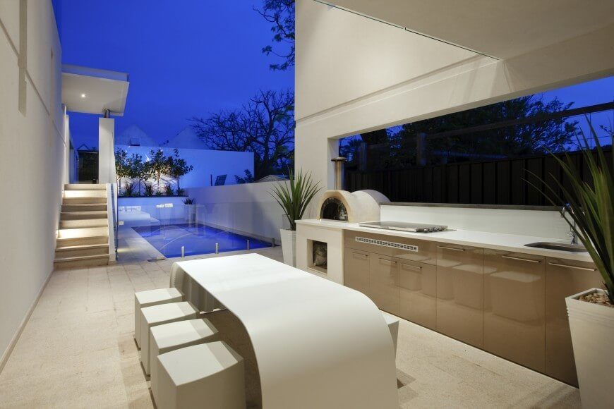 This simple outdoor kitchen embraces a modern design scheme and has a wood-fired oven.