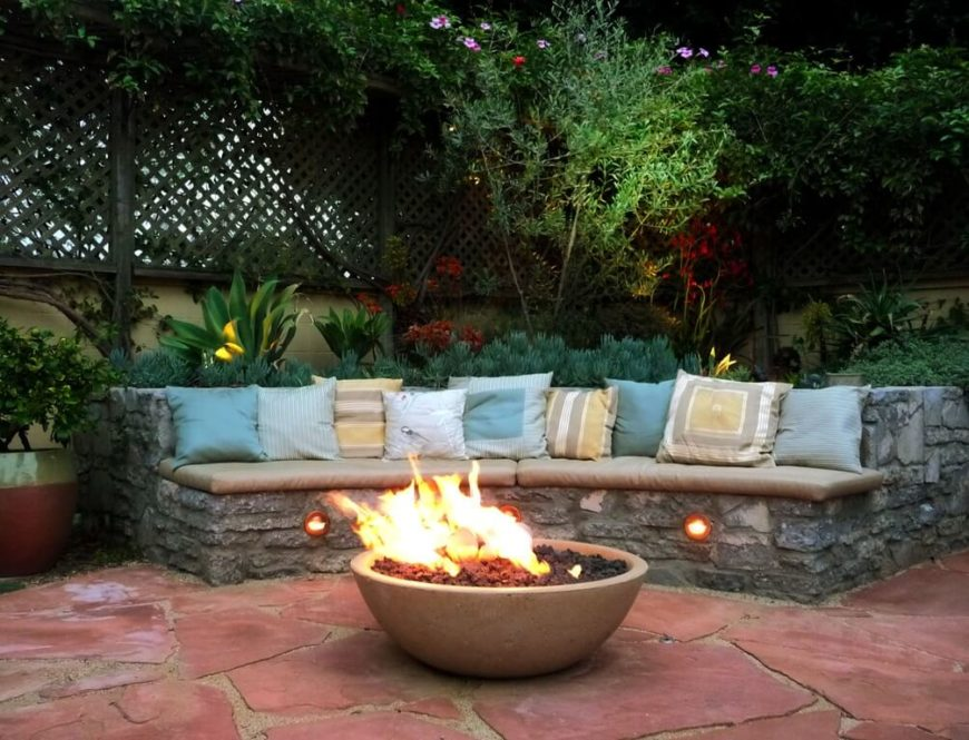 This is a unique sort of bench, constructed out of stone and padded with several cushions and many pillows. Lights have been installed in the bottom to illuminate the patio.