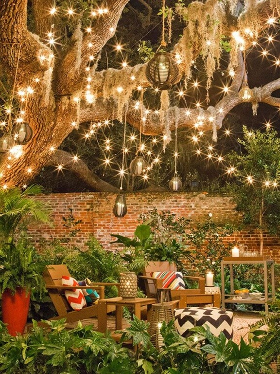 This space feels magical with the addition of lights and globes hanging from the gnarly branches of a willow tree. The adirondack chairs are nestled on a garden patio and accented with brightly patterned prints.