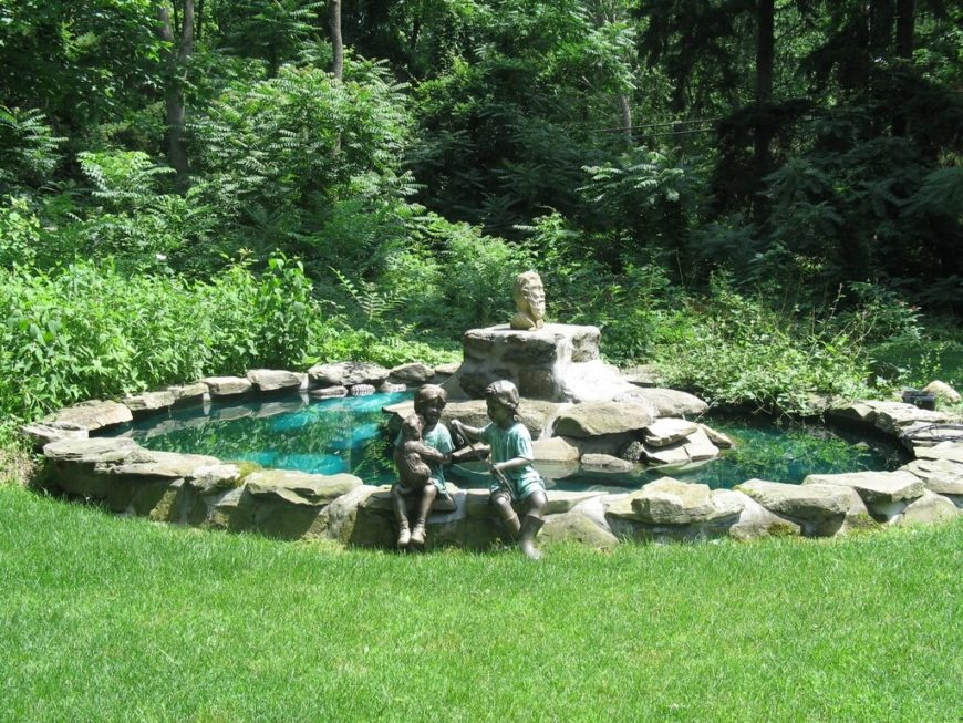 Statues can be placed on the edge of a pond, like these statues of children and a puppy placed as though sitting on the edge of this man made backyard pond.