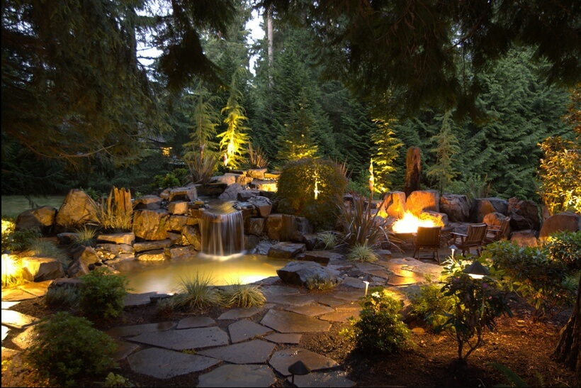 This is lighting done right. Aside from the bonfire in the fire pit, other lights are installed along the pathway, in the pond, and even above the small waterfall.