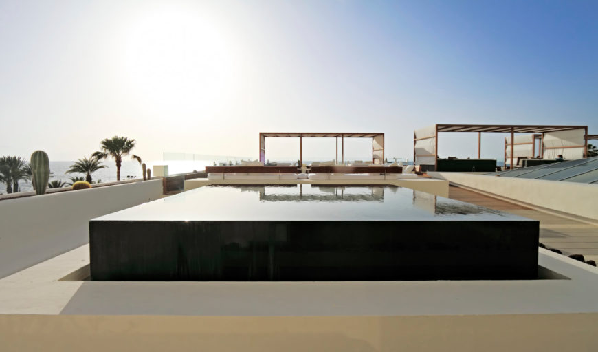 A small square raised infinity edge pool. This small dipping pool is great for space economy and is visually stunning. The back walls and infinity edge give this pool a super sleek and modern appeal.