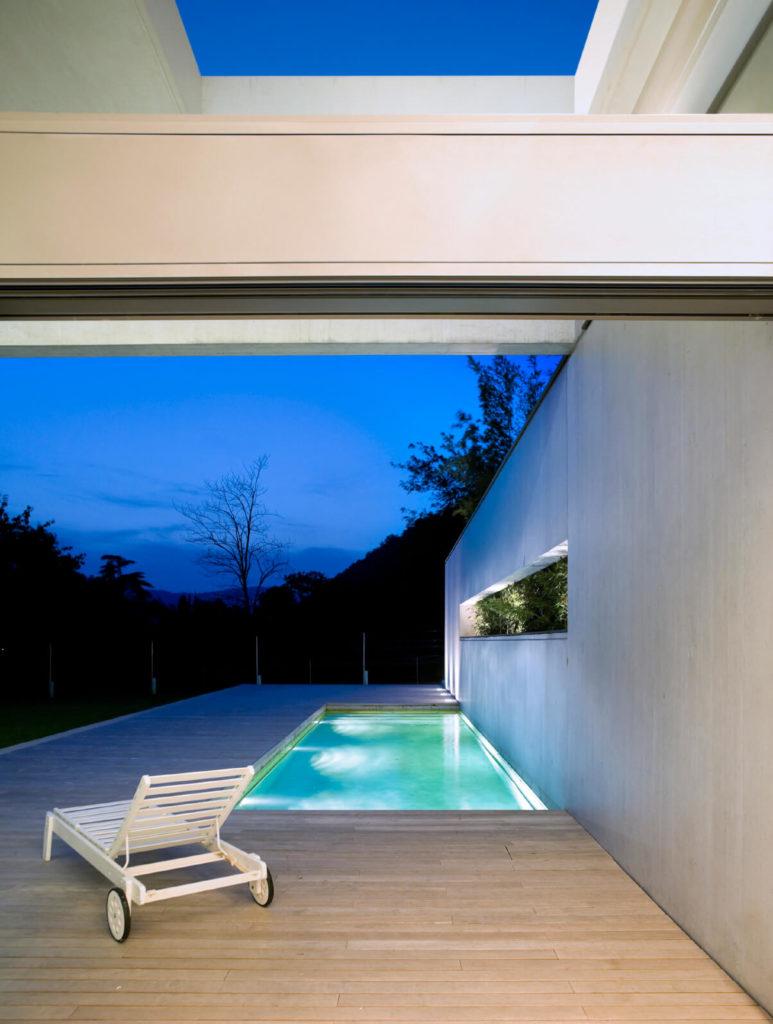 A tiny and sleek brightly lit pool tucked between a deck and the wall of the house. It's a clever use of space and creates and attractive and simple look.