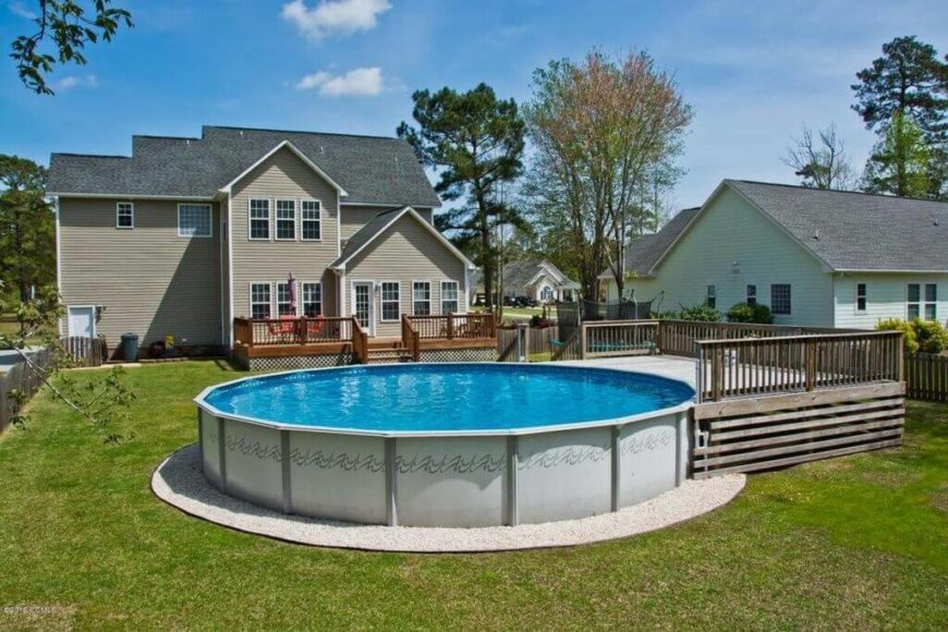 This round above-ground pool has a small deck on one end, but other wise is simple, and stands in the center of a mid sized yard. This shows that the above ground pool takes up far less space in the yard than an in-ground pool would.