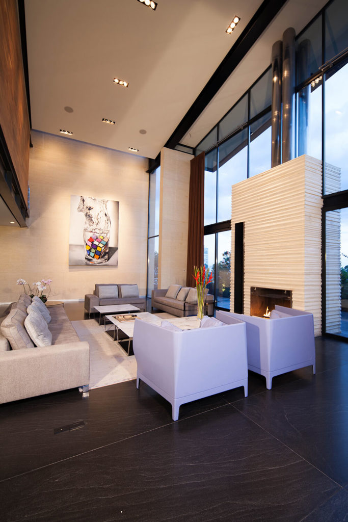 Within this cathedral-like two story room, we see an abundance of sharply designed furniture gathered before a large white stone fireplace, nestled in the exterior glazing.