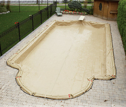 A standard winter cover in place, preparing this pool for the off season. The tarp here is weighted down by long bags filled with water. This helps keep the cover from blowing away. While these weights can hold down the cover against wind anything too heavy placed on the cover would sink into the water.