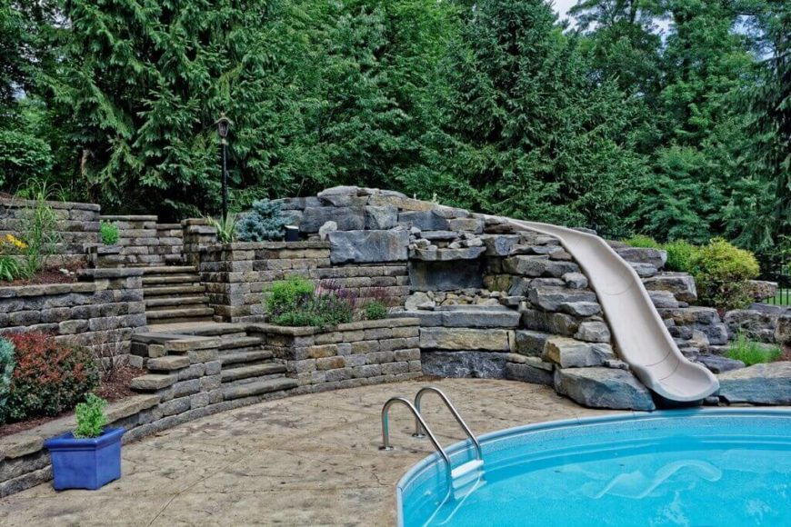 A pretty straight slides leads from the top of these stones, across the yard and into the pool. This is a great example of using landscaping and stone work to incorporate a slide into the rest of your yard.