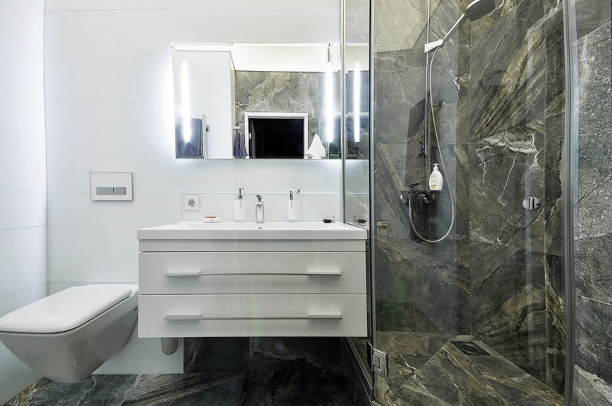 The bathroom may be small, but it is laid out in such a way that the space is maximized. The floor and shower are tiled in natural marble in a rich green-brown tone.