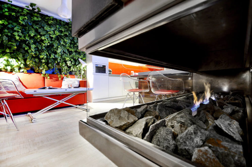 Here's a look through the floating fireplace at the open living room and kitchen area. The bright patches of orange truly jump out immediately, setting the stage for the whole space.
