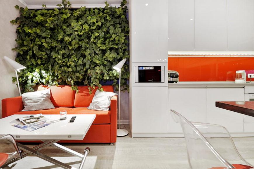 Glossy white cabinetry stands at great contrast to the lush wall garden, emphasizing the sharp mood of the home. An orange sofa matches the sleek backsplash seen at right.