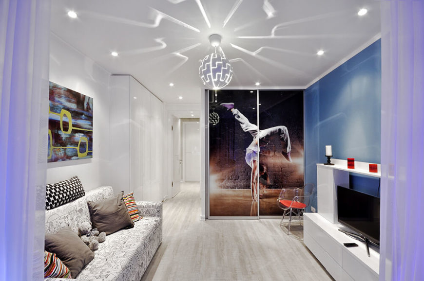 Here's a look at the primary bedroom sitting area, with the dressing room in the background. A sliding door entry is obscured by a large photo print. The disco-styled overhead light casts patterns over the white and blue space.