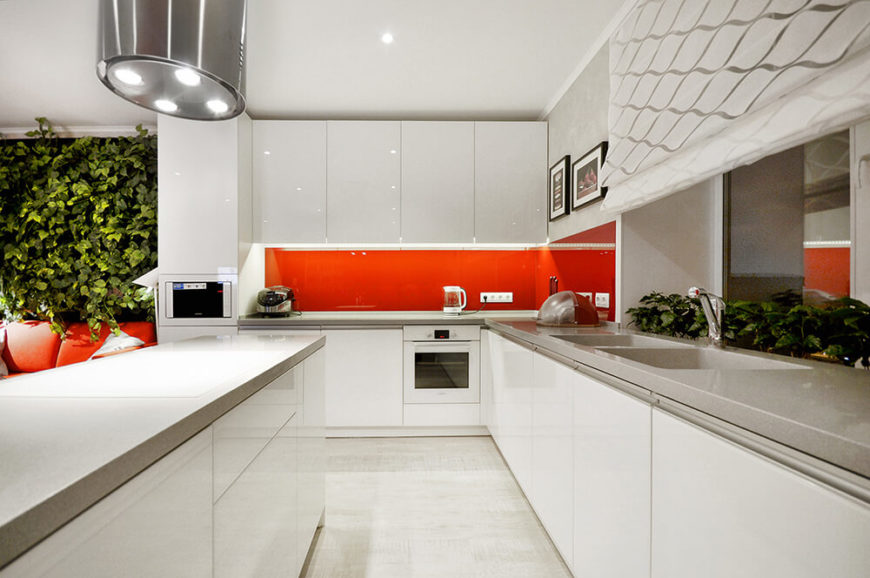 Here's a look at the bright white kitchen, flush with glossy white cabinetry and spiked with a bright orange backsplash. The hardware-less cupboard doors create a seamless environment.