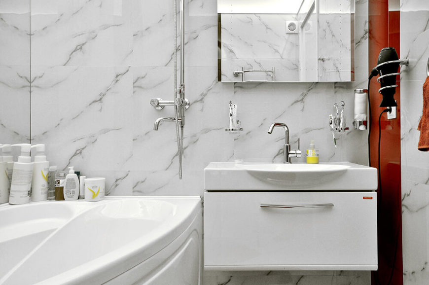 The bathroom is awash in marble, adding a sense of texture to the white surroundings. Even here, a dose of color adds tension and contrast.
