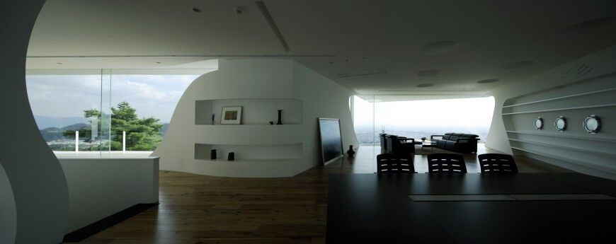 This built in shelving helps keep this unique space clutter free and open. It is minimalist living room, that uses space and shelving to stay as simple and sleek as possible.