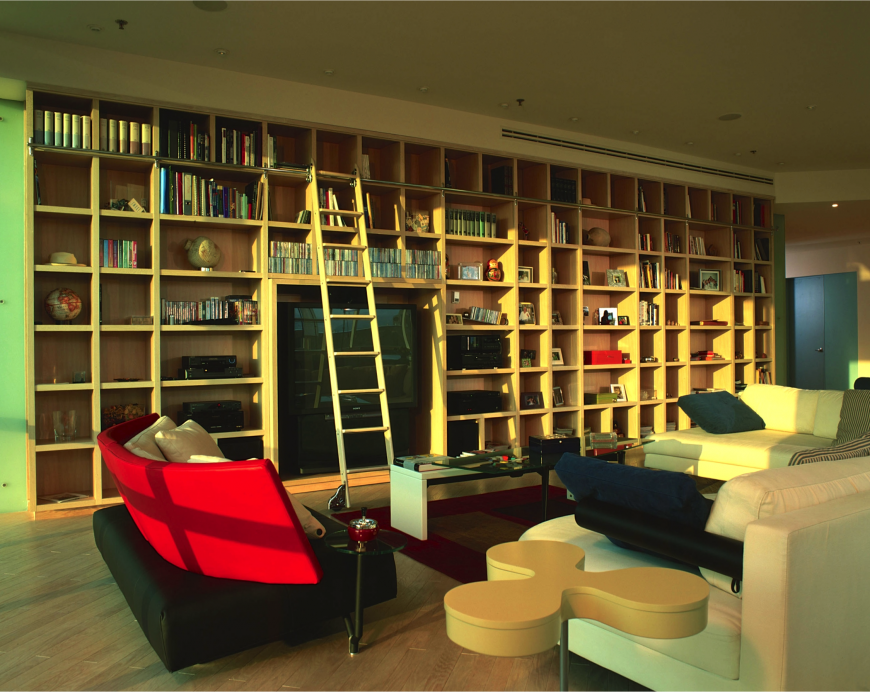 This living room has extensive shelving. So much so, there is a sliding ladder element. This gives the room a library stacks feel, that is unique and very visually interesting.