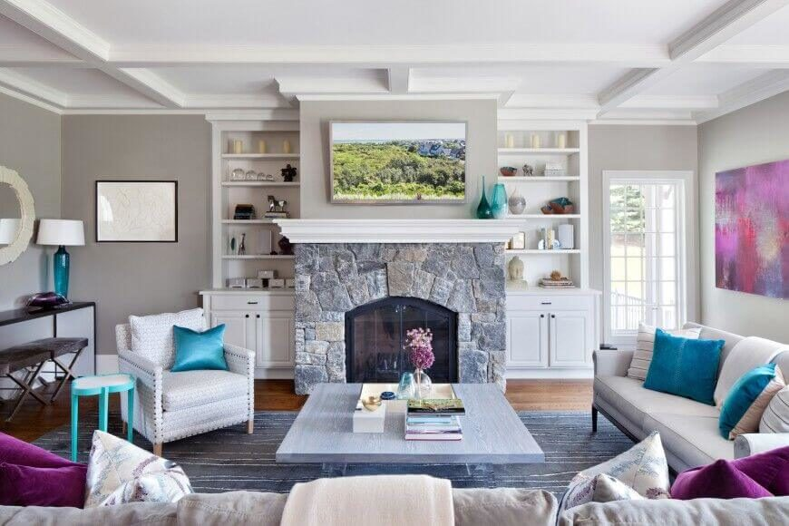 Two shelving areas on wither side of a stone fireplace. They serve to bookend the mantle, which also serves as additional shelving. There are decorative candles, and other design pieces that help fill the otherwise empty space with interesting design.