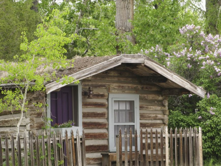 If you are looking for something simple and classic, consider the old-fashioned log cabin construction of this backyard building.