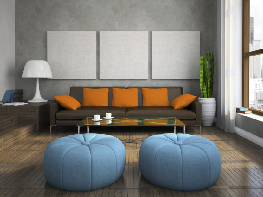 There are two round and interesting blue ottomans in this living room. These pouf style ottomans may not match the rest of the seating, but they add an incredible pop of color to balance out the orange.