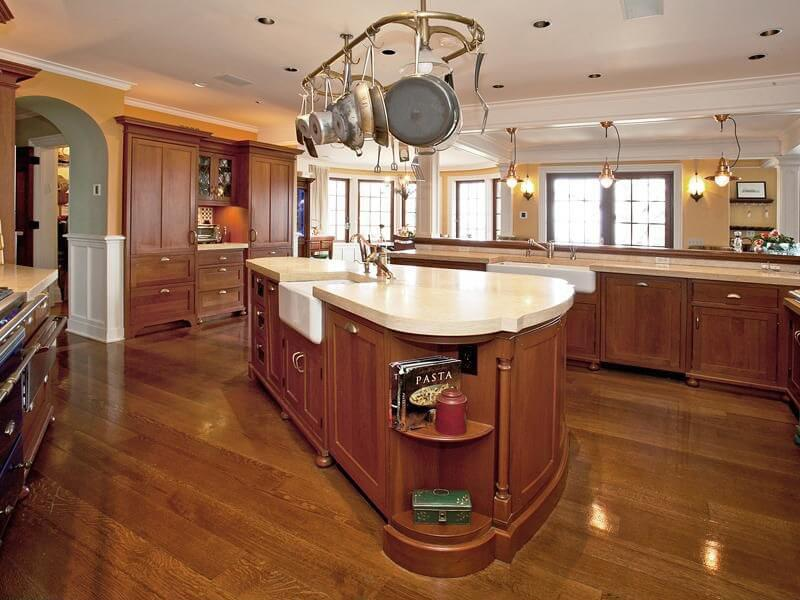 Pale solid surface countertops contrast with the rich wood throughout the rest of the kitchen.