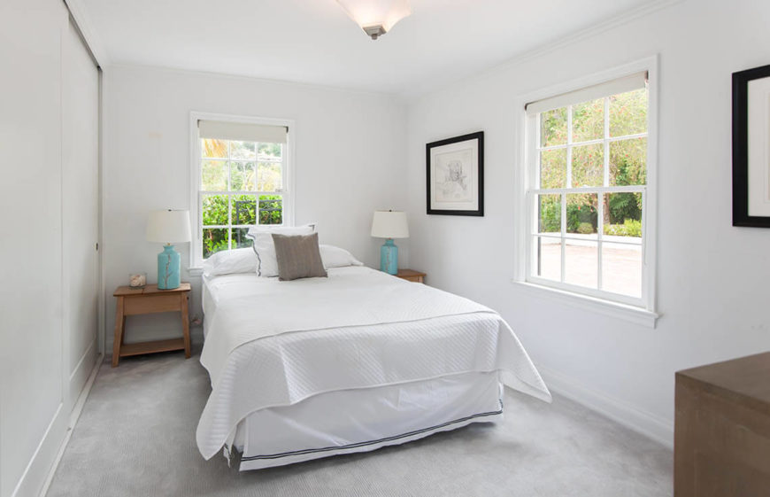 This small bedroom gets plenty of natural light through the two windows, but table lamps in an accent color are still added to complete the design. Again, we see how adding simple, impersonal prints can keep a bedroom feeling well-loved, but welcoming.