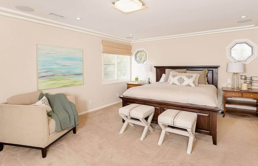 Cream and beige are neutral colors that keep your bedroom appealing to both men and women. The bed is dressed up by two small seats in front of the rich wood of the bed frame. A simple watercolor landscape painting brings color into the room.