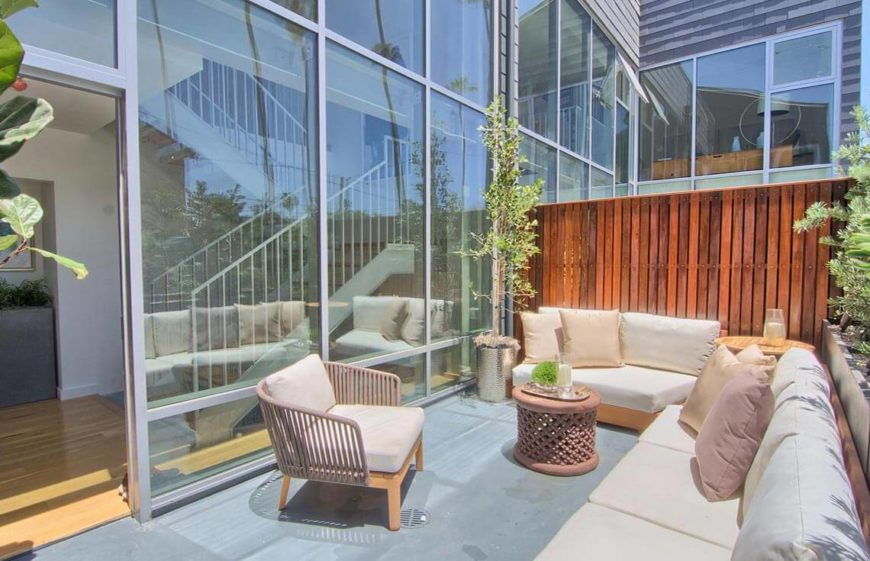This lovely staged patio shows the natural colors that look bright and inviting in the sun, and also lets prospective buyers project their own design ideas onto the space. The seating is arranged in a way to make a nice conversation area, a place where a party or gathering would fit perfectly. This patio invites people to just sit down and hang out. The plants are an amazing addition, bringing vibrancy and life to the area.