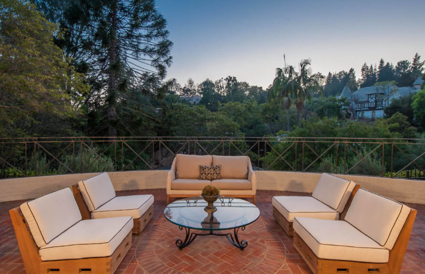 Here we see a circle of seats around a nice glass table. This makes a great gathering area for friends and family. Again we see a great use of neutral colors and furnished arrangements to make a welcoming and appealing space for buyers to really see the potential of this patio space.