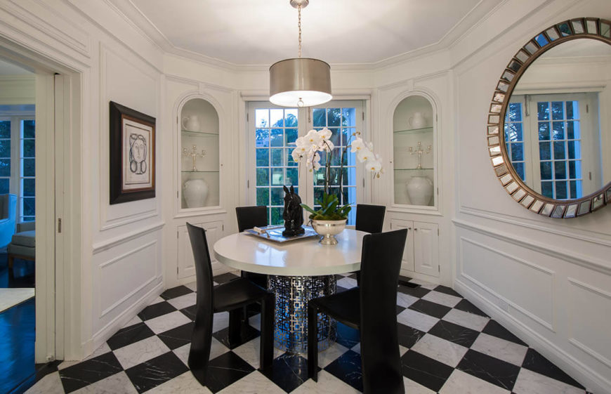 A simple and sophisticated dining room with a monochromatic theme. The windows try to let in a lot of natural light, but the lamps help when enough cannot shine in. While there is black in the room, there is plenty of white to balance it out and keep the room bright and welcoming. The room is not very large, so a smaller table is used to make a easy and open flow.