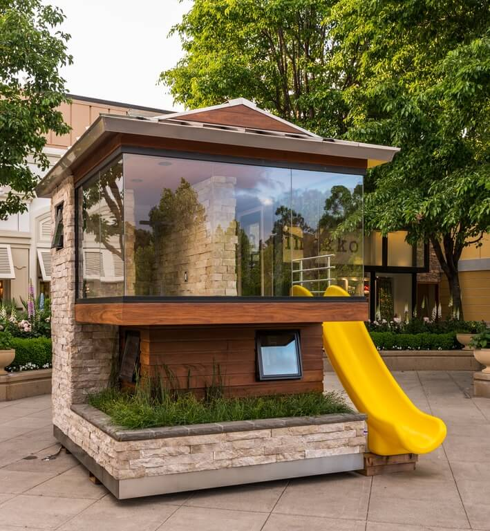 Stone detailing and glass walls make for an ultra modern and chic play structure. If you have a modern style home, consider building a modern style play structure to match.