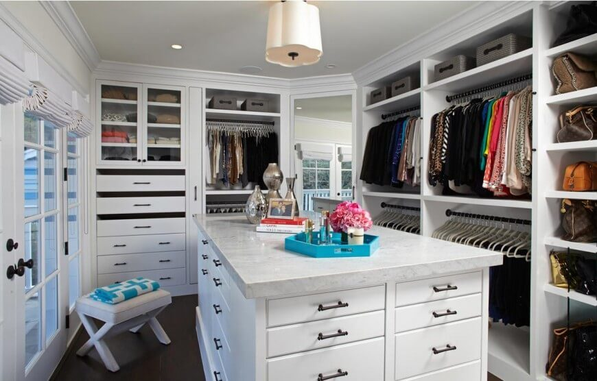 "This incredible walk-in closet still has lots of clothes in it, but all the hangers match, purses and shoes are in designated areas, and only a few neat accessories are sitting out on the ""island""."