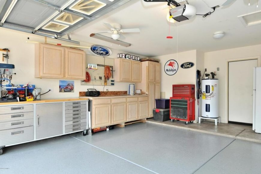 This garage is painted in light colors and a large workspace has been set up with simple cabinetry, a pegboard, and lots of lighting.