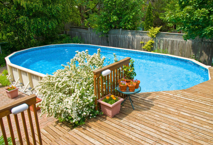 This is a great example of a above ground pool with a deck around one side, and landscaping to enhance the area.