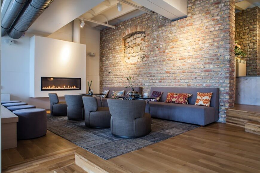 Here is a room with drywall on the far side and a beautiful exposed brick along the back of the room. This room has an incredible amount of space, and the brick works with this space to give it a classic industrial look.