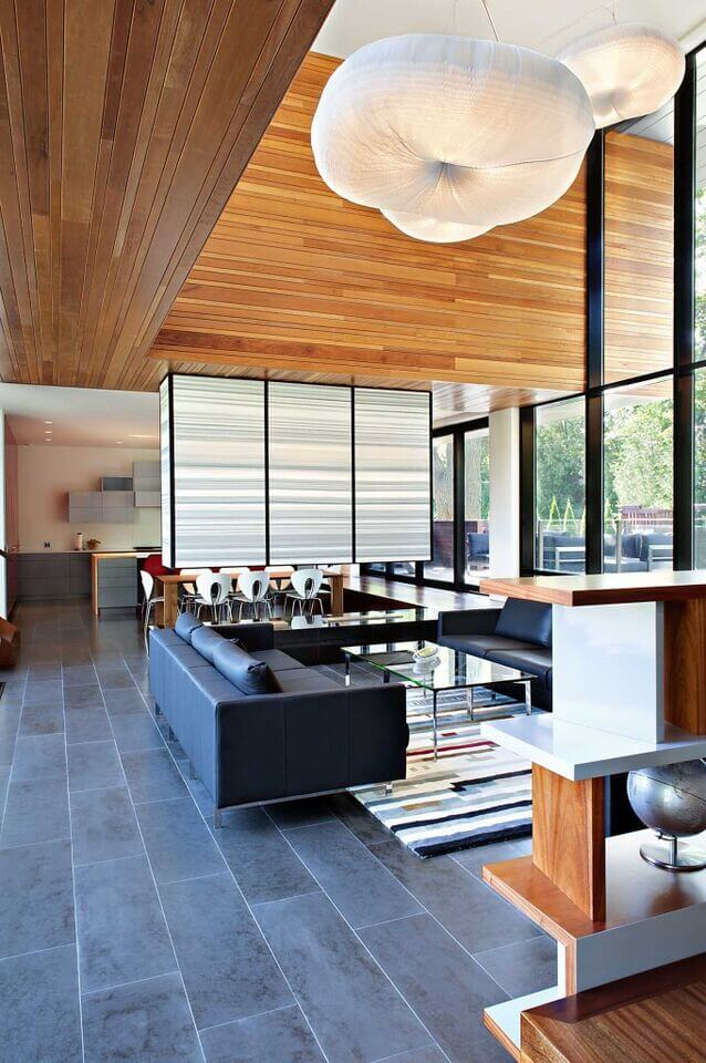 Here is a stunning wide open living room with simple walls, and a large wooden wall hanging above the space. This finished and bright wooden wall brings some natural tones to this modern and sleek living space.