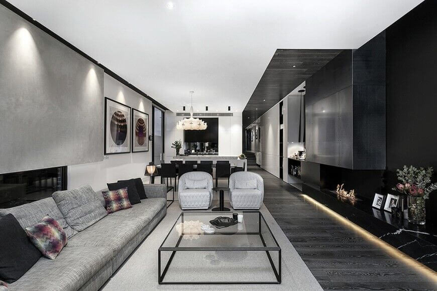 Here is a living room with multiple wall types that all add different elements to this simple and minimalist living room. One thing you can do on your walls when you hang art is to have lighting highlight those artworks. This can draw the eye, and make them stand out.