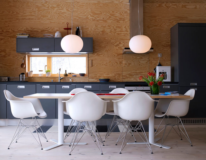 The open plan design of the interior allows the dining and kitchen functions to overlap in a broad, minimalist space. Here we see warm natural wood tones mixing with sleek dark cabinetry with the large white dining table at center.