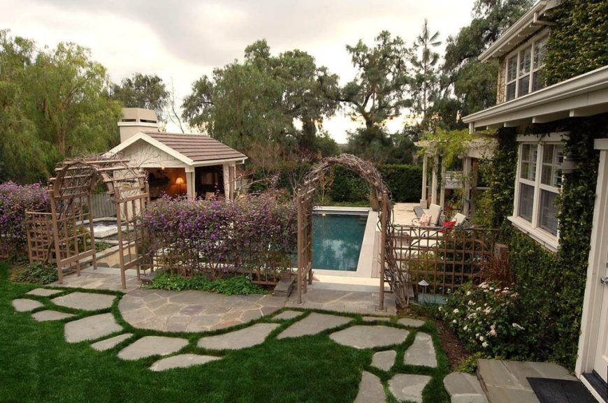 this beautiful vine covered home has two cedar arbors leading into the pool area - Arbor Design Ideas